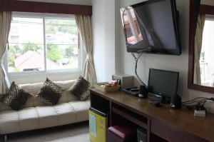 Forest Patong Hotel room with sofa, flat TV and desk